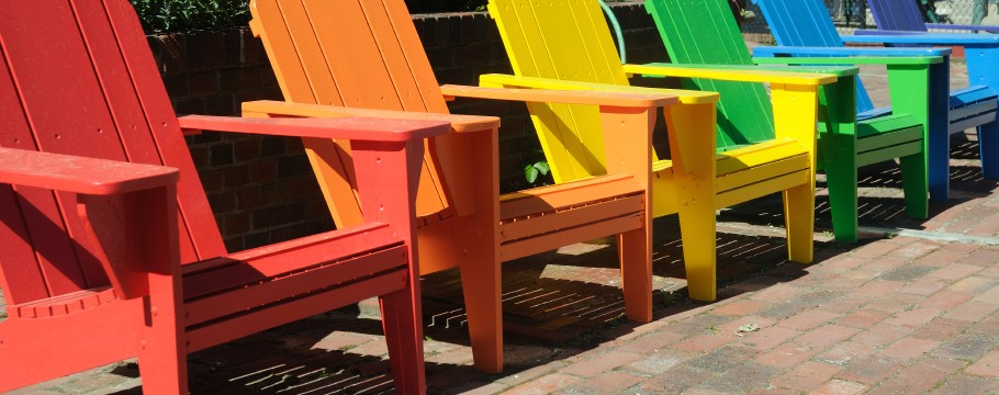 A row of brightly painted Adirondack Chairs at an Inn in Provincetown, Massachusetts. Chairs are  painted in the same colors and arrangement as the Gay Pride flag.